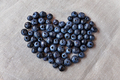 Blueberry heart  lie on a homespun tablecloth. Rustic cozy background with healthy food.