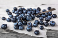 Blueberries lie on a homespun tablecloth. Rustic cozy background with healthy food.