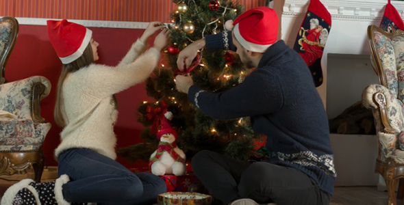 Young Couple Decorates a Christmas Tree
