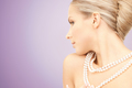 beautiful woman with pearl necklace over violet