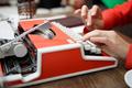 woman at table typing on typewriter