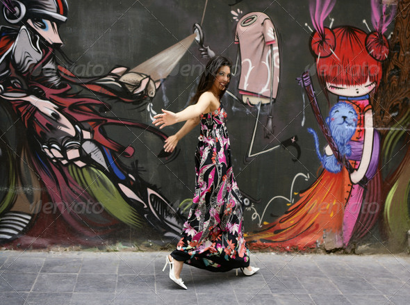 Elegant fashion woman running over urban graffiti - Stock Photo - Images