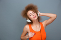 Relaxed carefree curly woman in earphones listening to music