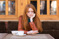 Pretty thoughtful girl with red hair drinking coffee outdoor