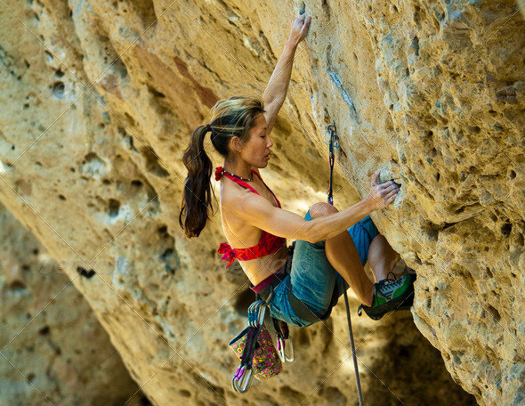 Female rock climber clinging to a cliff - Stock Photo - Images