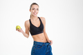 Sportswoman in big jeans became skinny and holding an apple