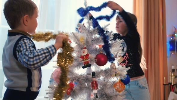 Children Decorating Christmas Tree With Tinsel