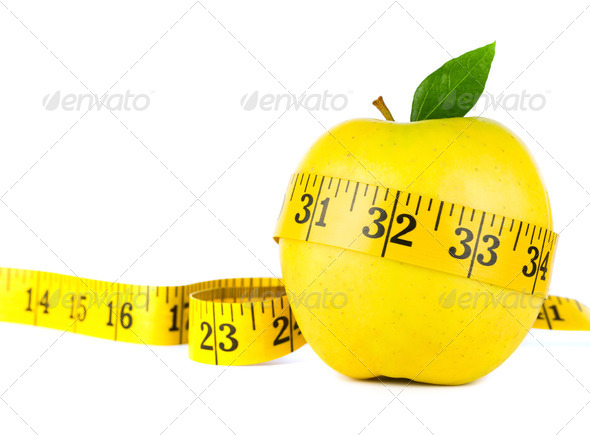 Yellow apple surrounded by measuring tape  - Stock Photo - Images