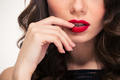 Tempting red lips of curly woman touched by her hand