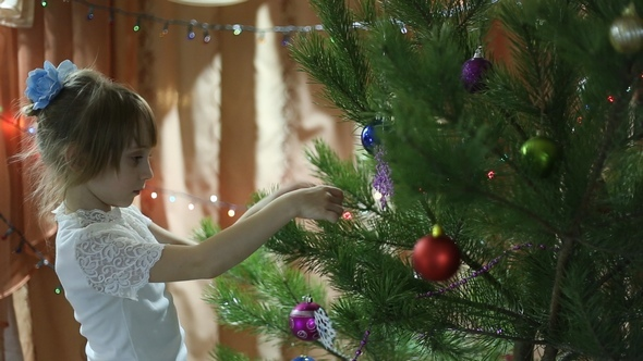 Girl Hanging Toys on the Christmas Tree