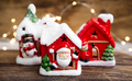 Christmas houses decorations with festive lights on wooden board