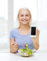 smiling woman with smartphone eating salad at home