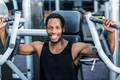 Smiling man using exercise machine at the gym