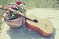 Guitar, basket with wine and bouquet of flowers. Vintage tender