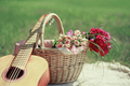 Guitar, basket and bouquet of flowers. Vintage tender background