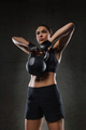 young woman flexing muscles with kettlebell in gym