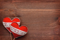 Two felt hearts with laces, symbol of love, on wooden background