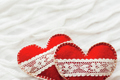 White fabric background with ruche.Two felt hearts with laces, s