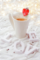 White cup of hot coffee with decorative heart and engagement dia
