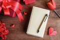 Blank notebook with red gift box and flower on wooden background, Valentines concept