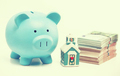 Real estate sale savings, loans market. Piggy bank home and pile of euro cash