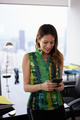 Young Latina Woman Text Messaging On Phone In Office