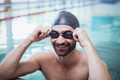 Smiling man wearing swim cap and goggles at the pool
