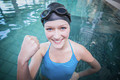 Fit woman wearing swim cap and goggles with raised fist in the pool