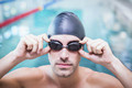 Handsome man wearing swim cap and goggles at the pool