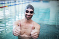 Smiling man wearing swim cap and goggles with thumbs up at the pool