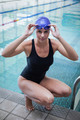 Pretty woman crouching and wearing swim cap and goggles at the pool