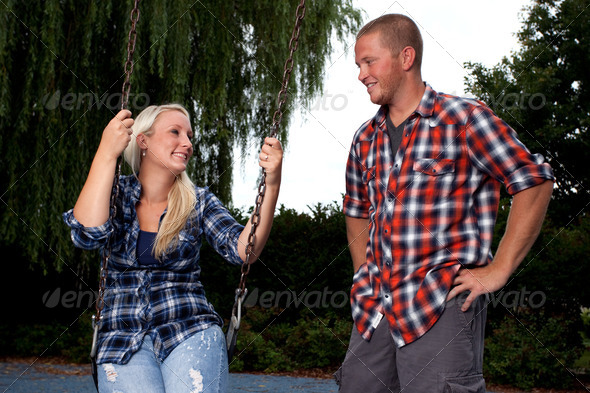 Young Couple on Swingset - Stock Photo - Images