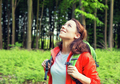 Woman hiker in forest smiling looking up enjoying freedom