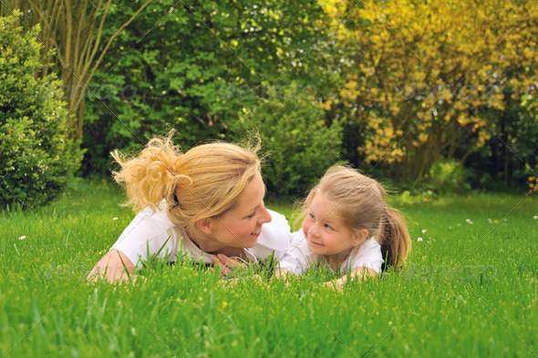Young woman and little girl  relaxing on the grass - Stock Photo - Images
