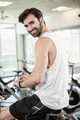 Smiling man on exercise bike using smartwatch at the gym
