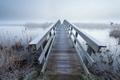 wooden bridge via river in winter