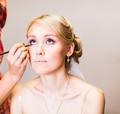 Make-up artist doing make up for young beautiful bride applying wedding make-up