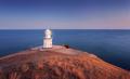 Beautiful white lighthouse on the ocean coastline at sunset. Lan