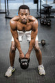 Shirtless man lifting heavy kettlebell at the crossfit gym