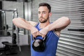 Muscular man lifting heavy kettlebell at the crossfit gym