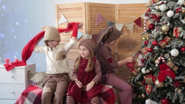 Children Sit By The Christmas Tree And Play