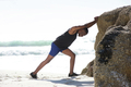 Man sport training exercise stretching legs at the beach