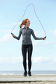 Young woman skipping with jump rope outdoors