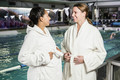 Pregnant women with bathrobe talking at the swimming pool