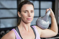 Smiling woman holding heavy kettlebell a the gym