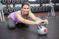 Smiling woman exercising with kettlebell at the gym