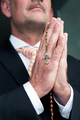 businessman praying with rosary