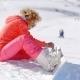 Skier Putting On Her Snowboard