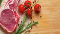 Pieces of crude meat with rosemary and tomatoes.