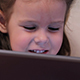 Little Girl Watching a Cartoon on the Electronic Tablet